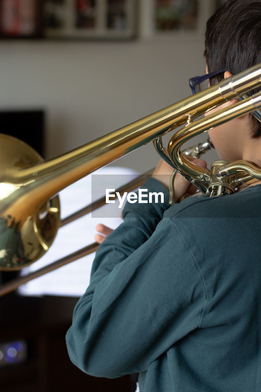 Rear view of boy playing trumpet at home