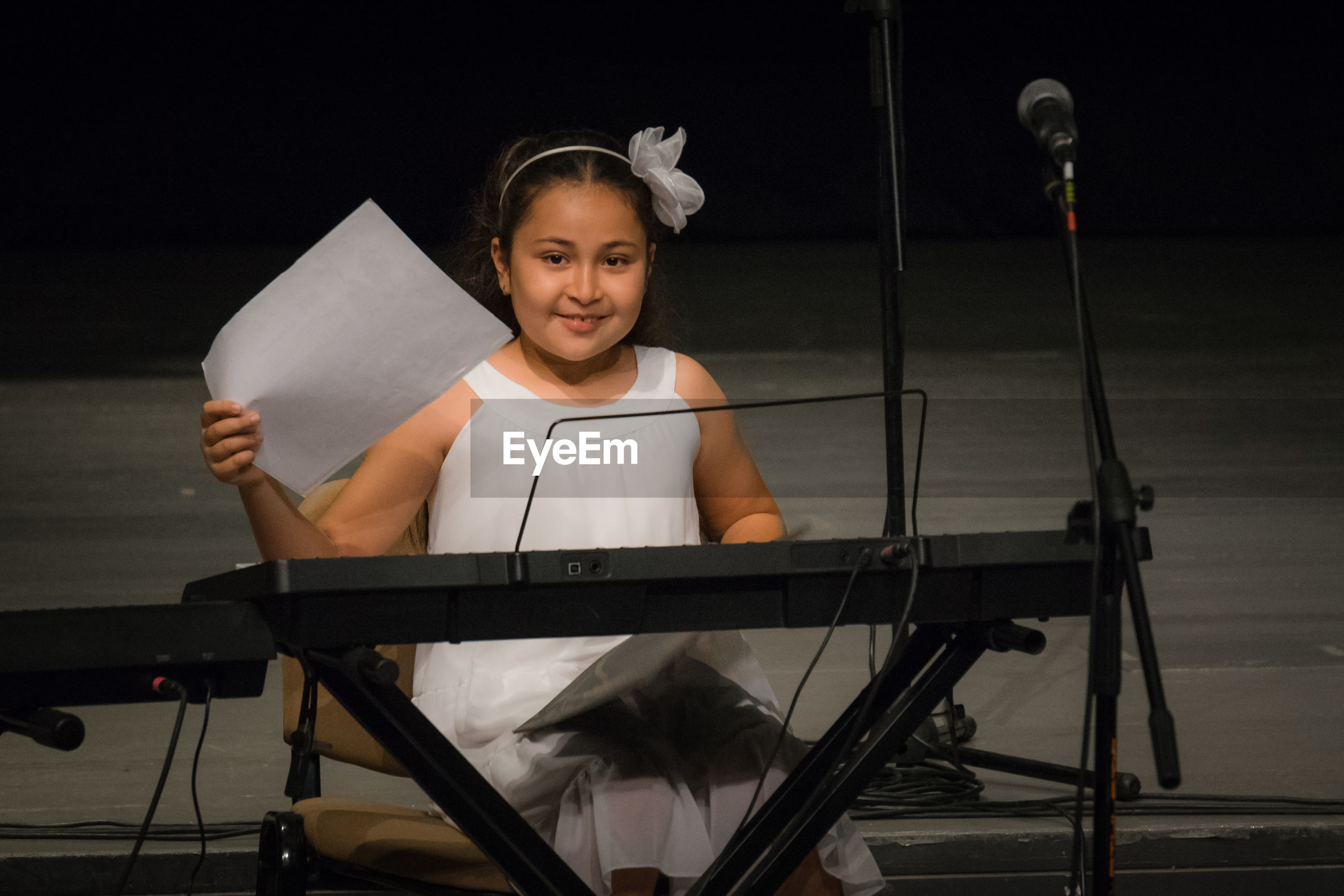 Portrait of smiling girl with piano on stage