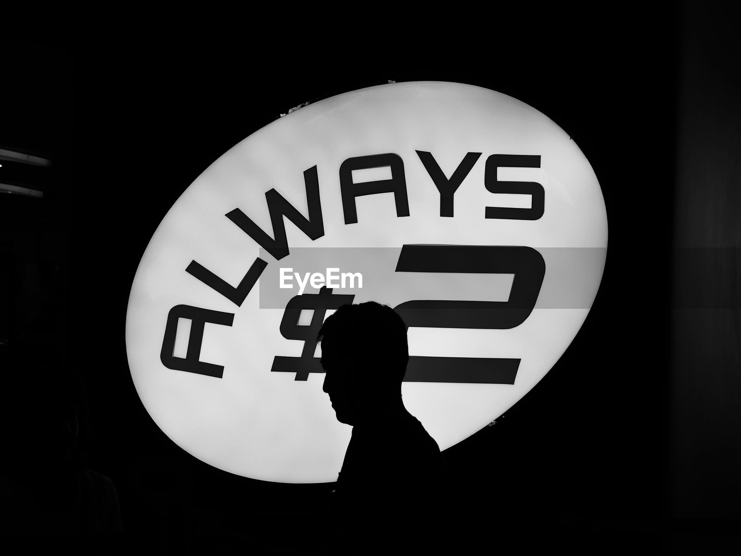 Silhouette of person in front of illuminated sign board
