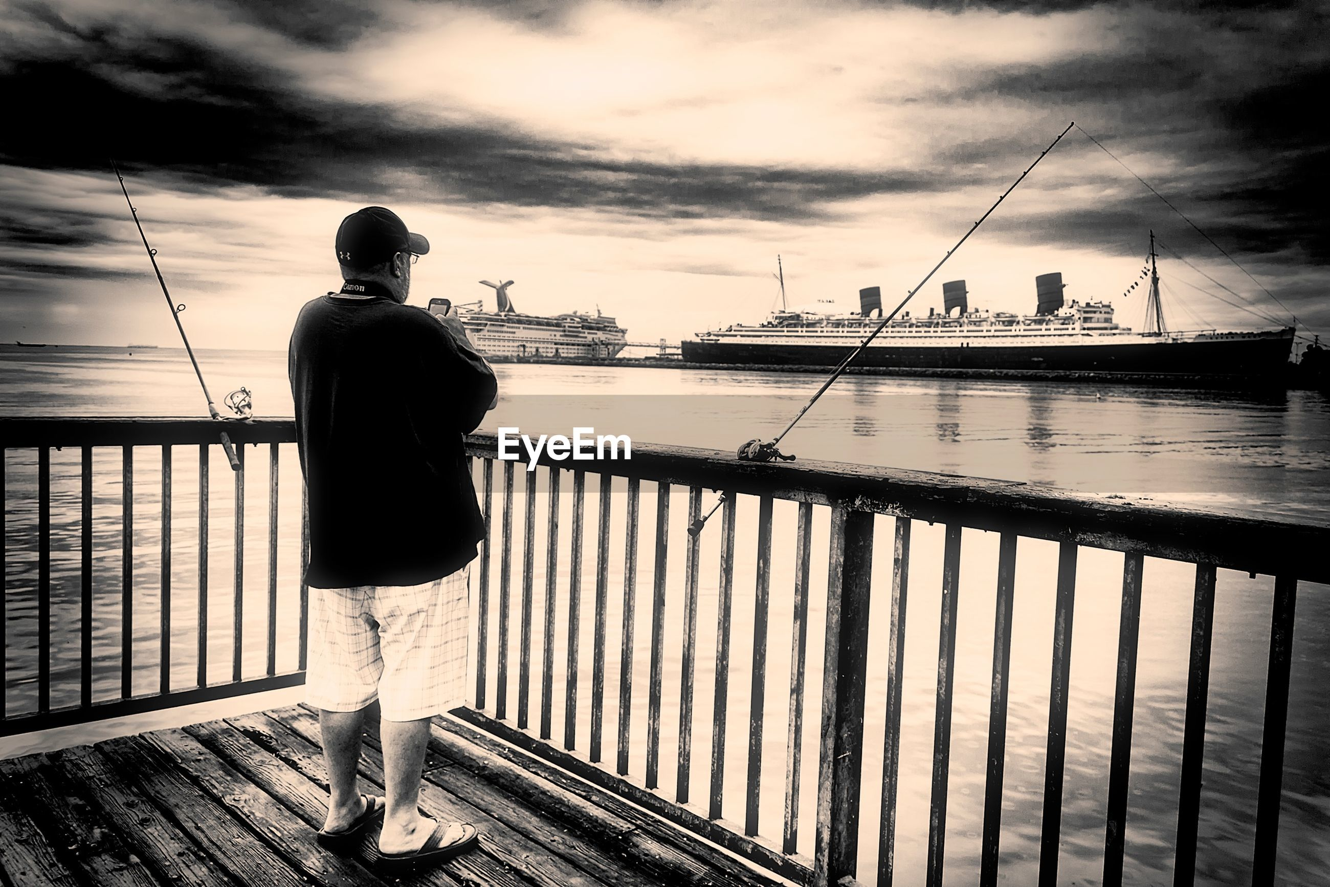water, sky, sea, rear view, pier, standing, full length, cloud - sky, railing, lifestyles, men, leisure activity, cloud, nature, cloudy, casual clothing, fishing, tranquility