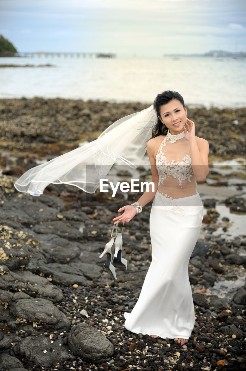 Full length portrait of smiling bride holding high heels while standing at beach