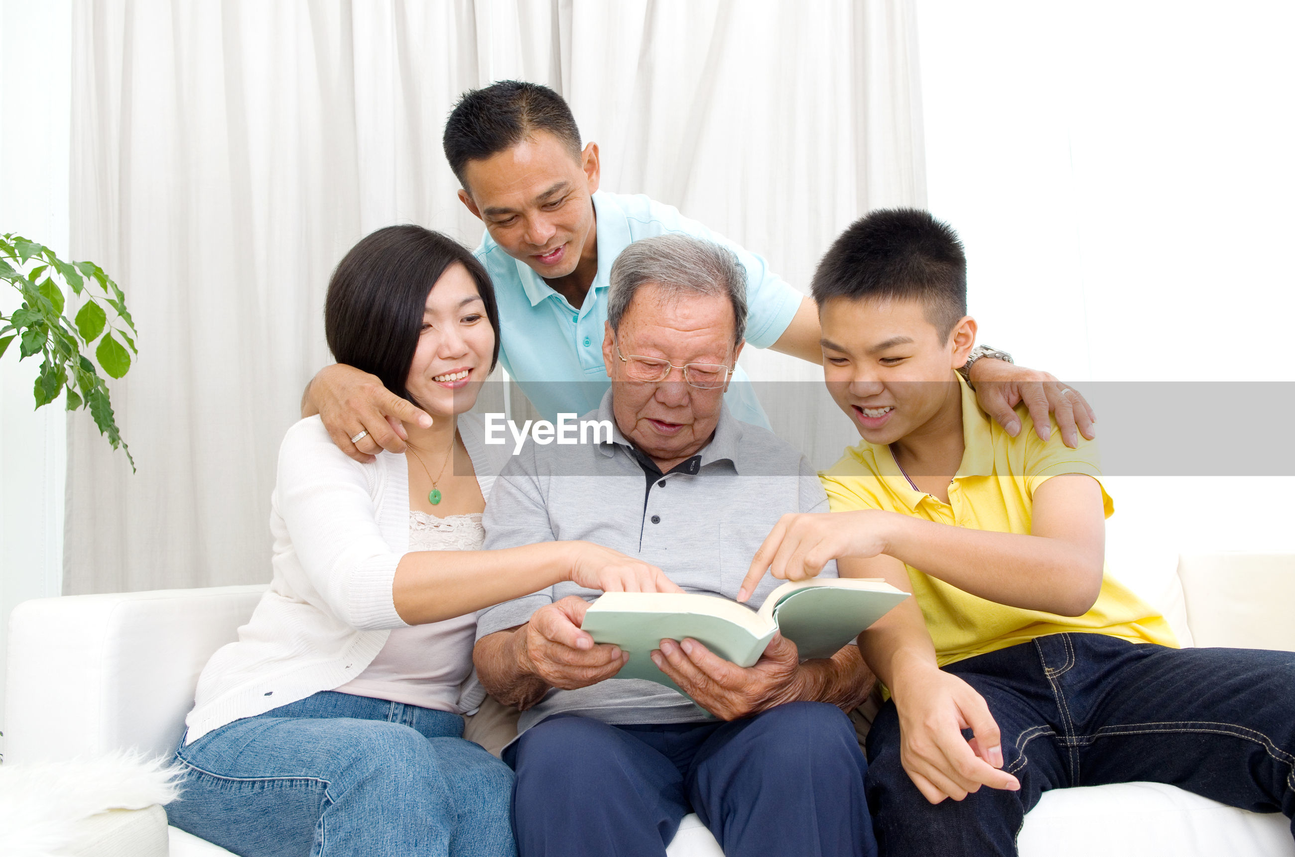 Family reading book on sofa at home