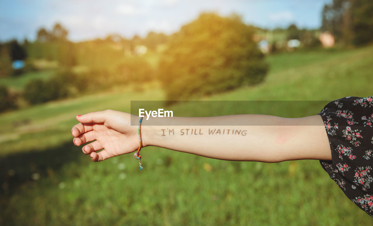 Cropped Hand Of Woman Showing Text Written On Forearm At Park