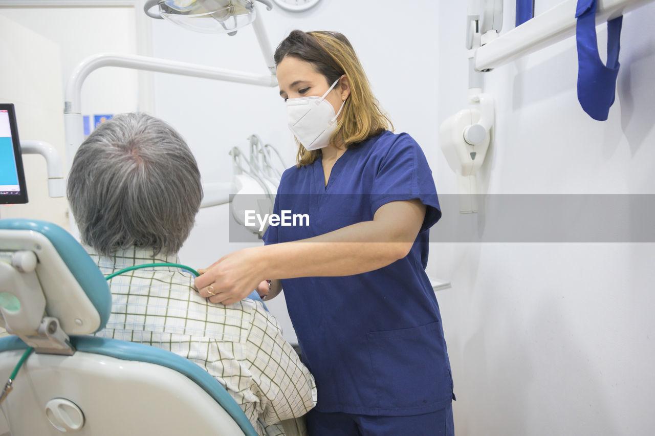 Dentist examining patient at clinic