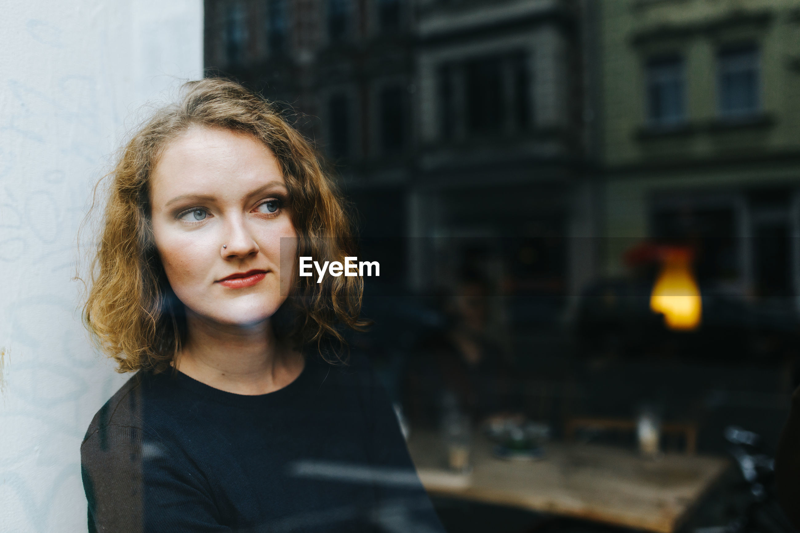 Thoughtful woman looking through window at cafe