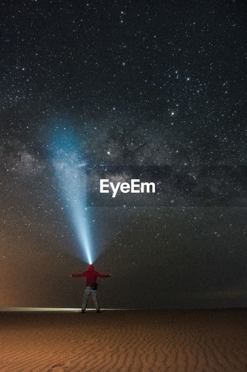 Man With Illuminated Headlamp Standing At Beach Against Star Field