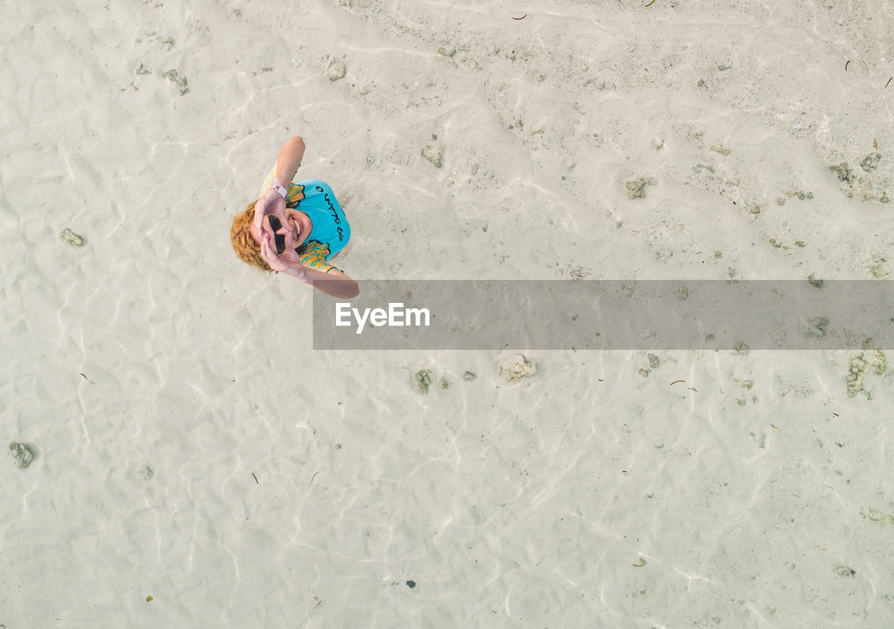 high angle view, leisure activity, beach, one person, land, full length, childhood, sand, real people, day, child, nature, lifestyles, holiday, vacations, men, trip, lying down, males, outdoors, innocence
