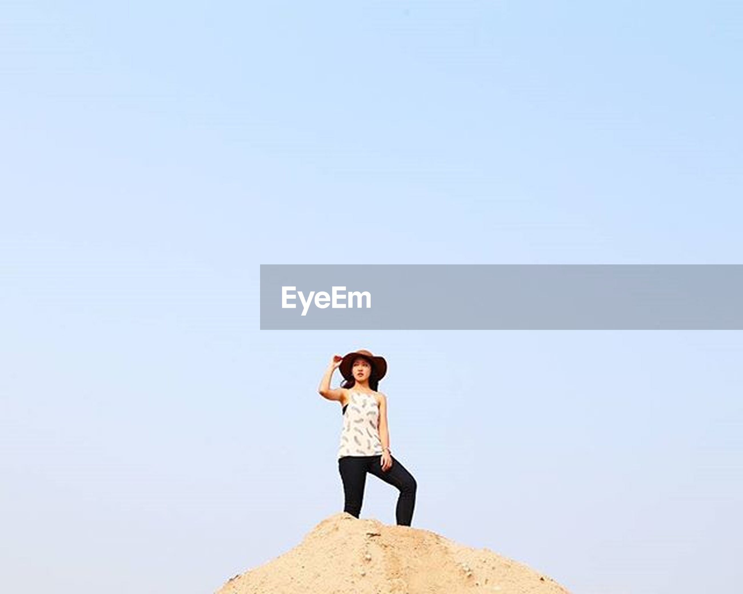 copy space, full length, lifestyles, rear view, clear sky, standing, casual clothing, leisure activity, young adult, person, tranquility, sitting, rock - object, tranquil scene, looking at view, nature, getting away from it all, young women