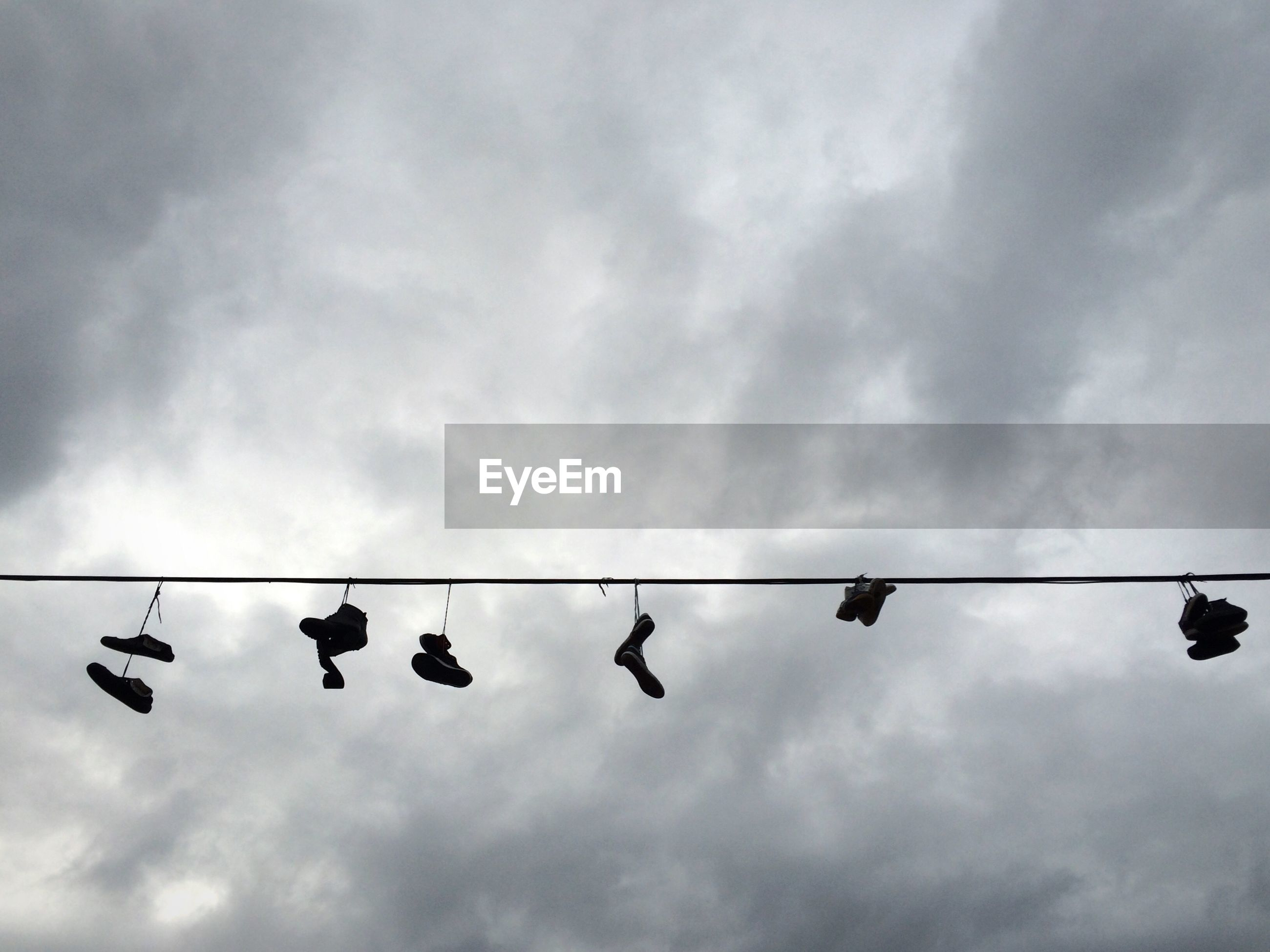 Low angle view of shoes hanging on rope against sky