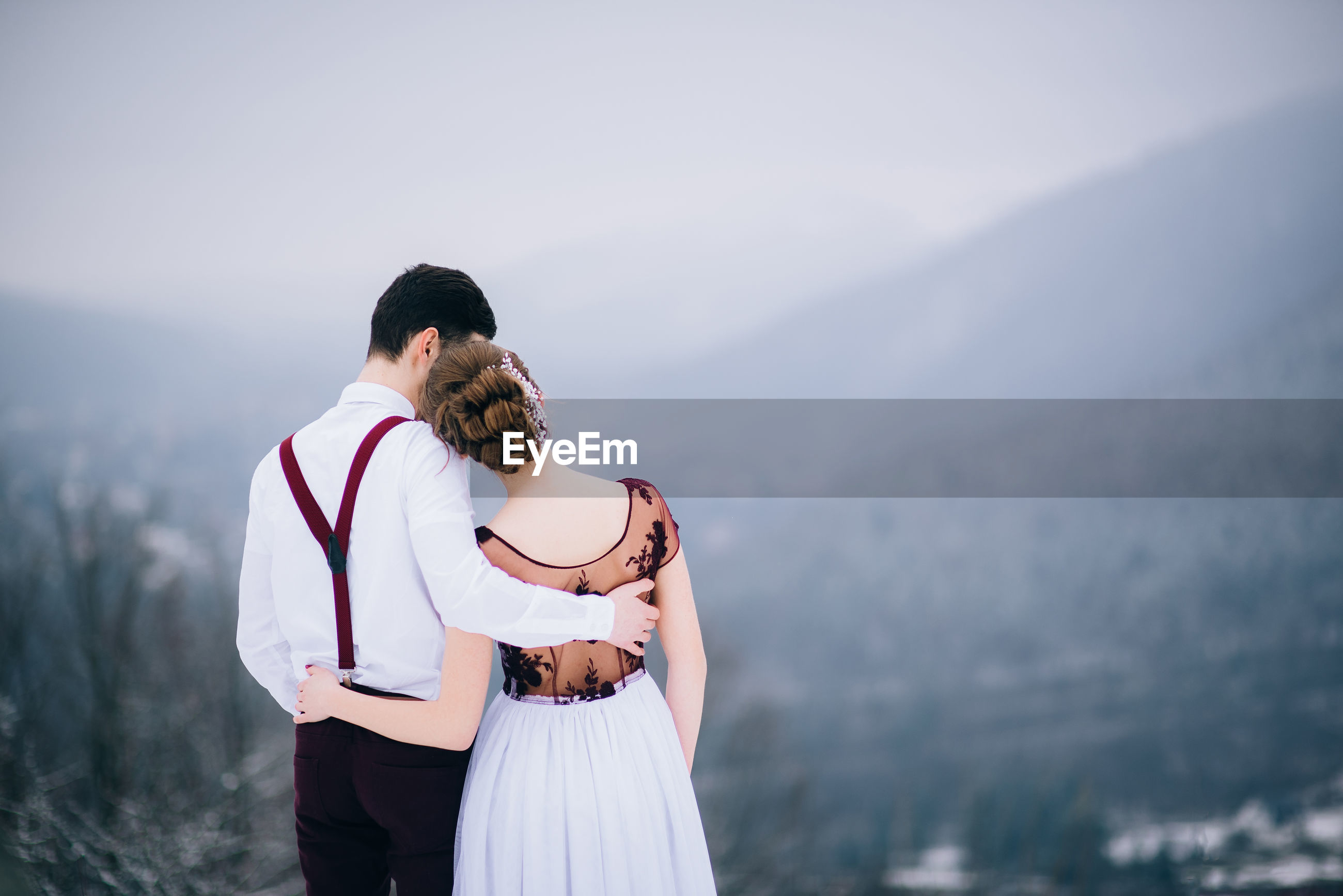 COUPLE STANDING ON MOUNTAIN AGAINST MOUNTAINS