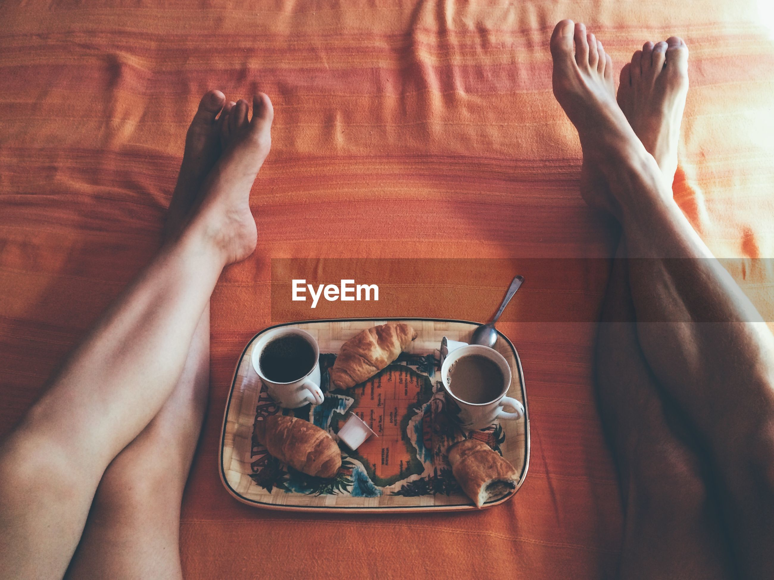 Low section of naked man and woman relaxing by food tray on bed