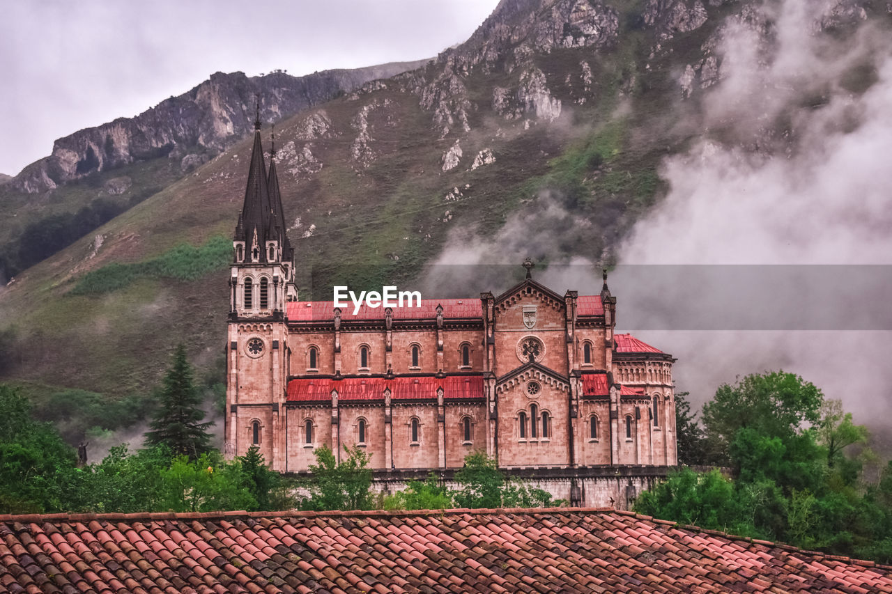 architecture, built structure, building exterior, mountain, building, sky, nature, roof, tree, travel destinations, day, no people, residential district, house, old, plant, tourism, cloud - sky, smoke - physical structure, outdoors, roof tile