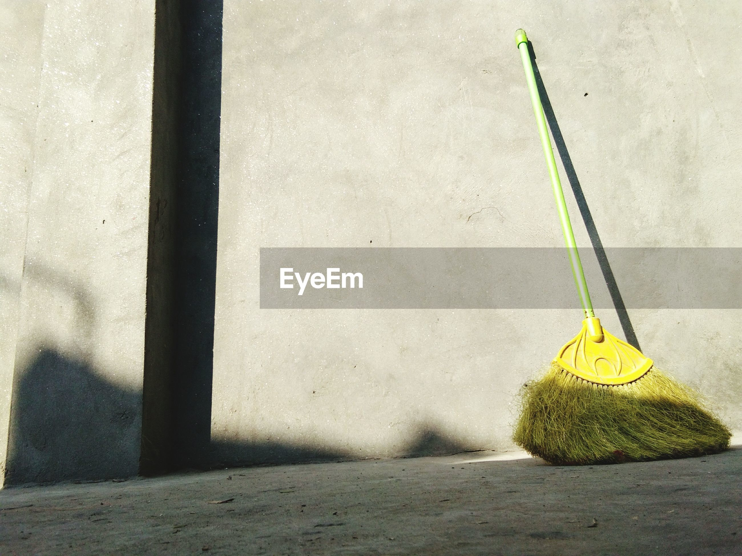 Broom on footpath against concrete wall during sunny day
