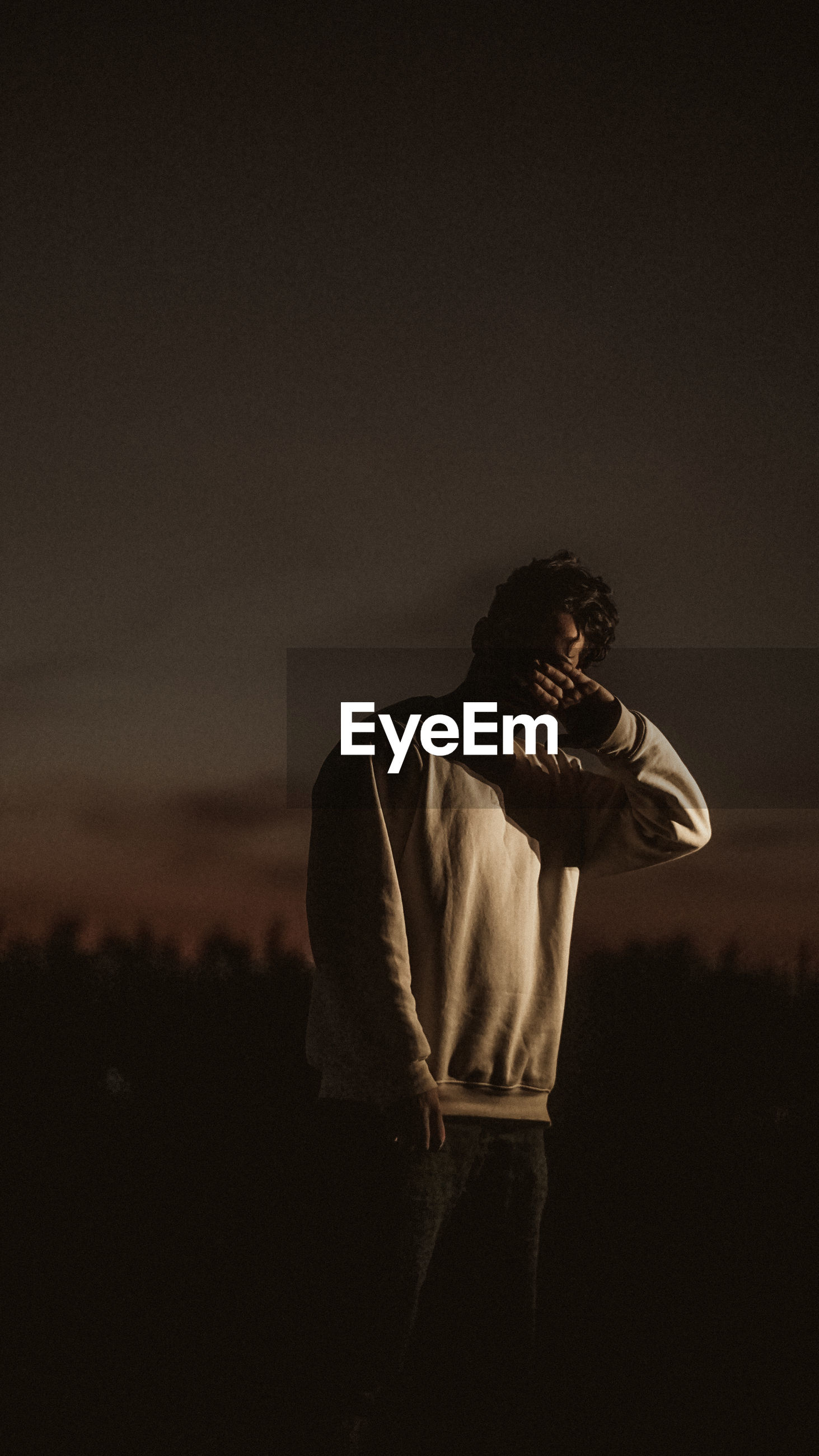 Young man looking away against sky at night