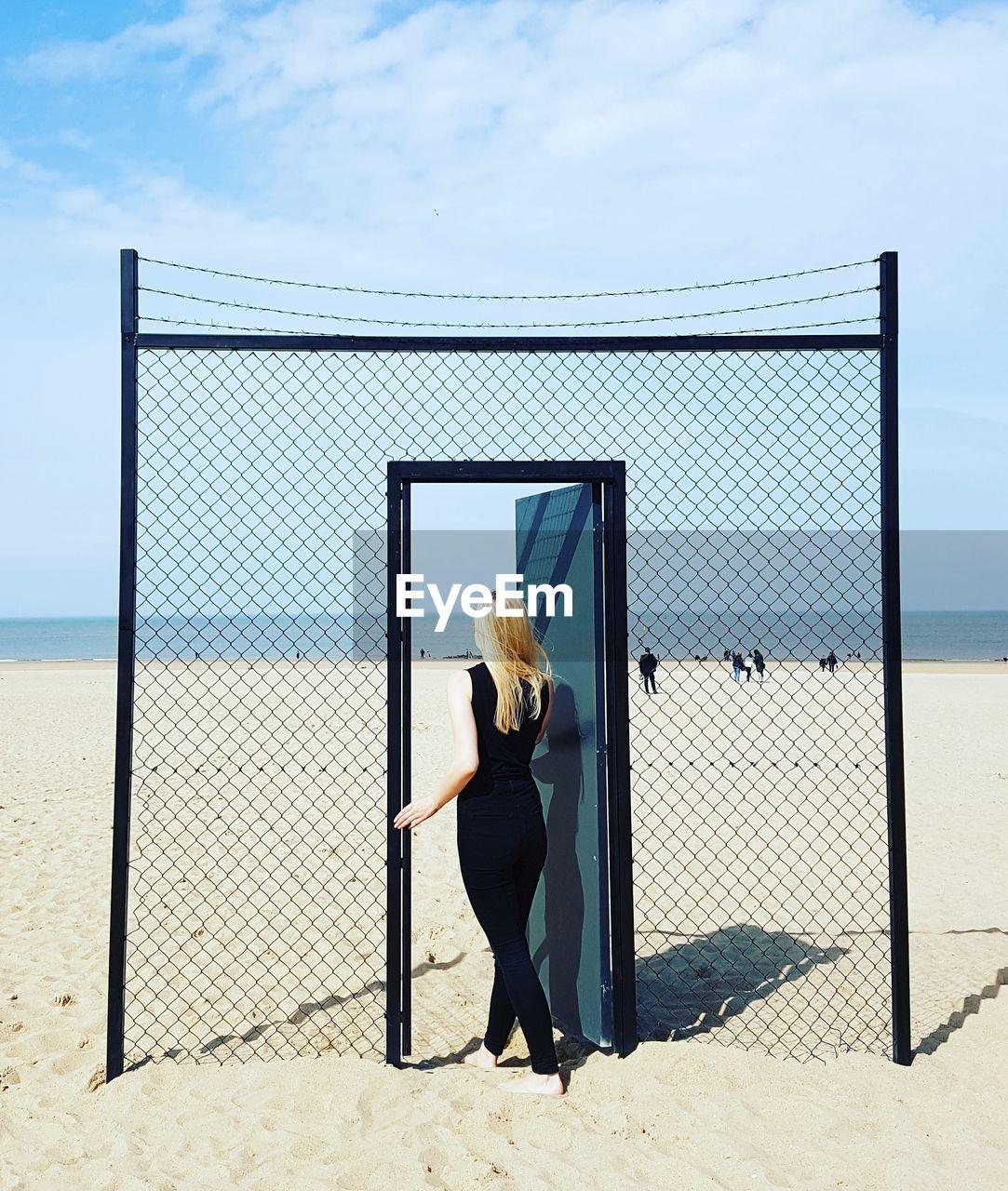 Full Length Of Woman Walking On Doorway At Beach Against Sky