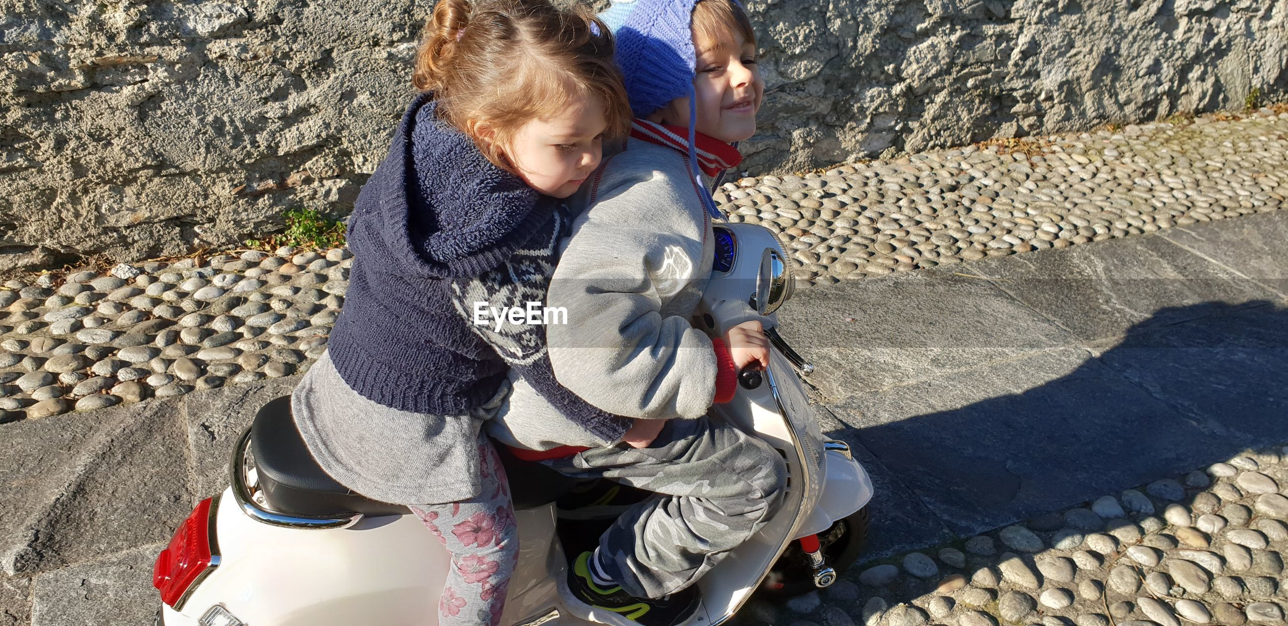 High angle view of siblings riding motor scooter on footpath