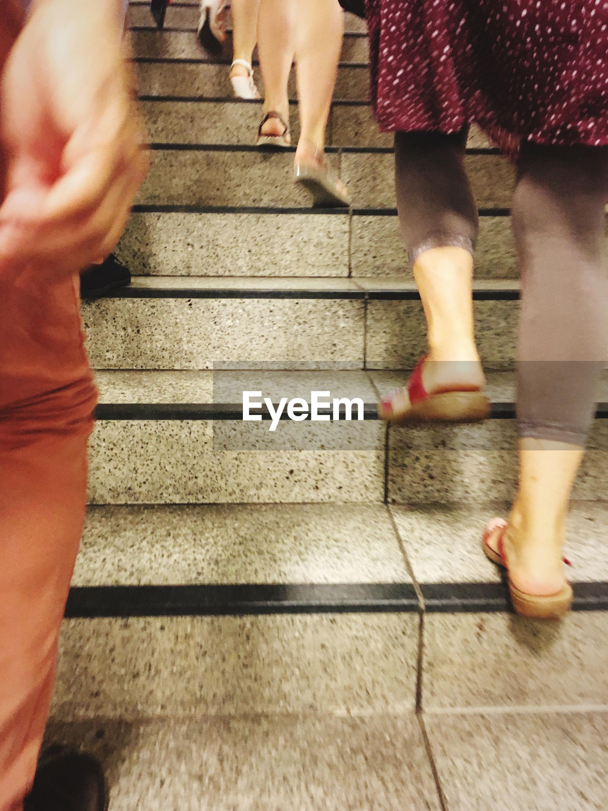 LOW SECTION OF WOMEN WALKING ON STEPS