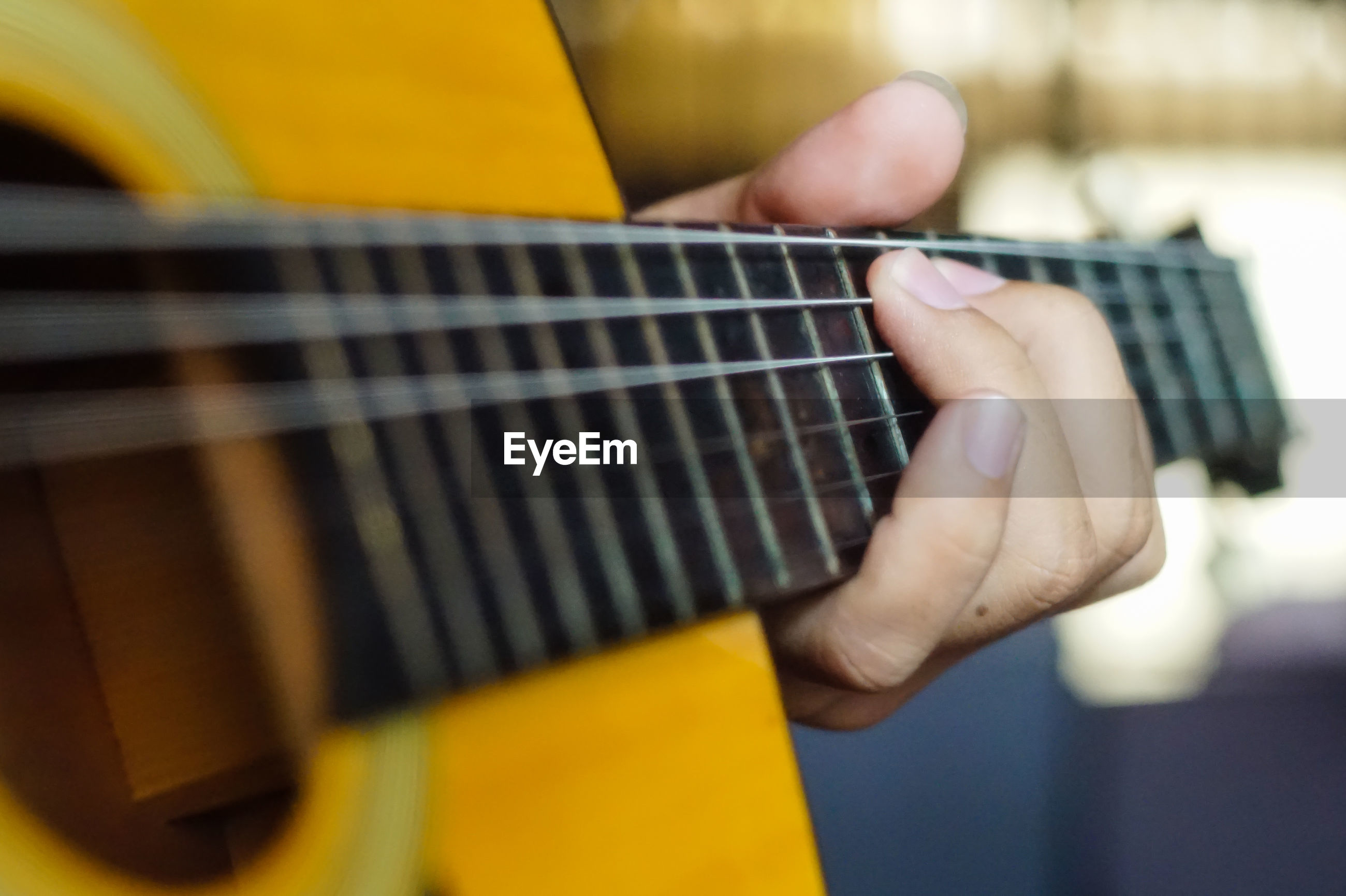 Cropped hand of person playing guitar