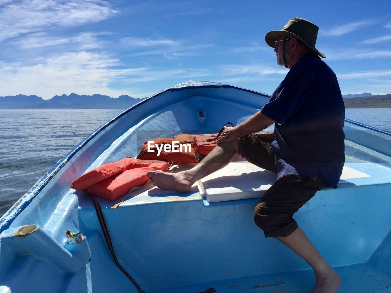 Side view of men on boat in sea against sky