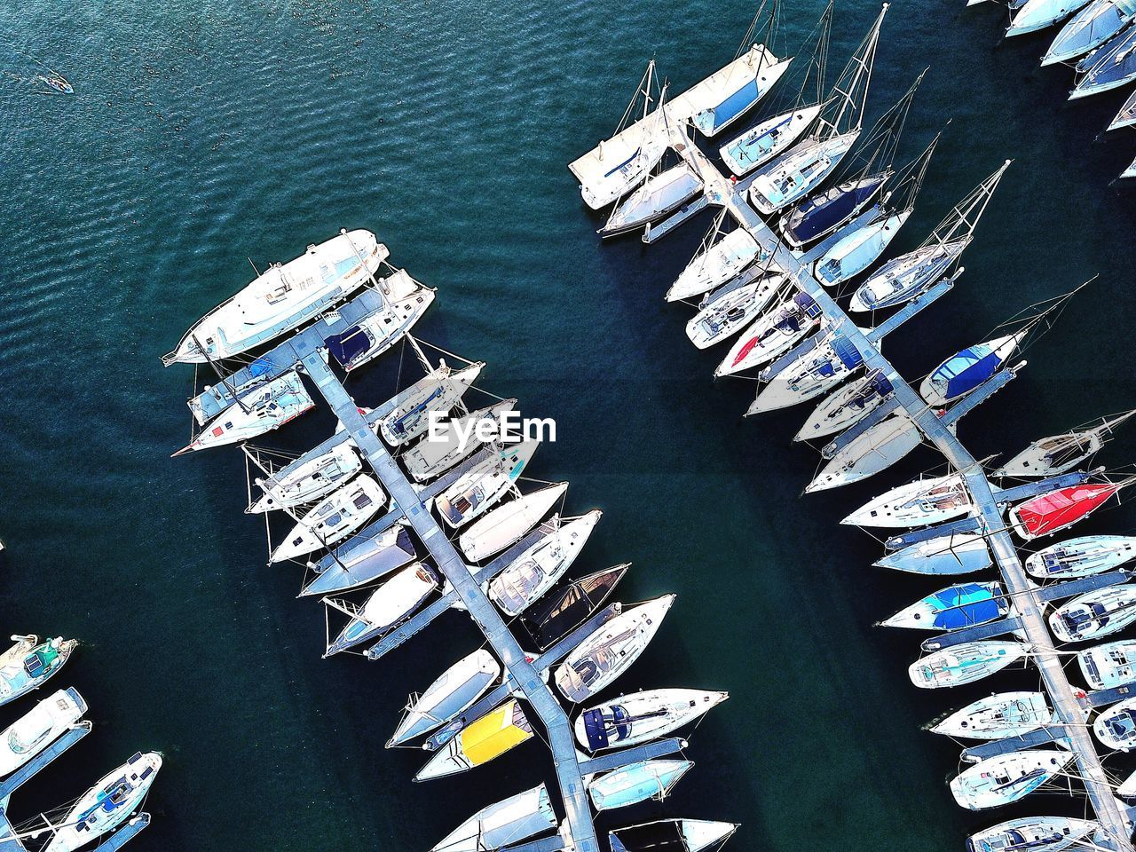 water, nautical vessel, transportation, high angle view, mode of transportation, moored, day, nature, no people, sea, in a row, waterfront, sunlight, outdoors, large group of objects, harbor, travel, pier, abundance, yacht, rowboat