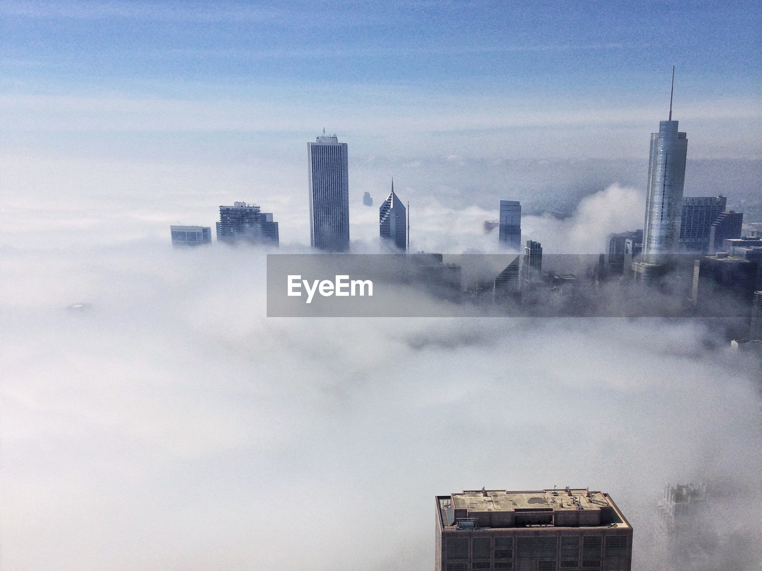 Buildings in city against sky during foggy weather