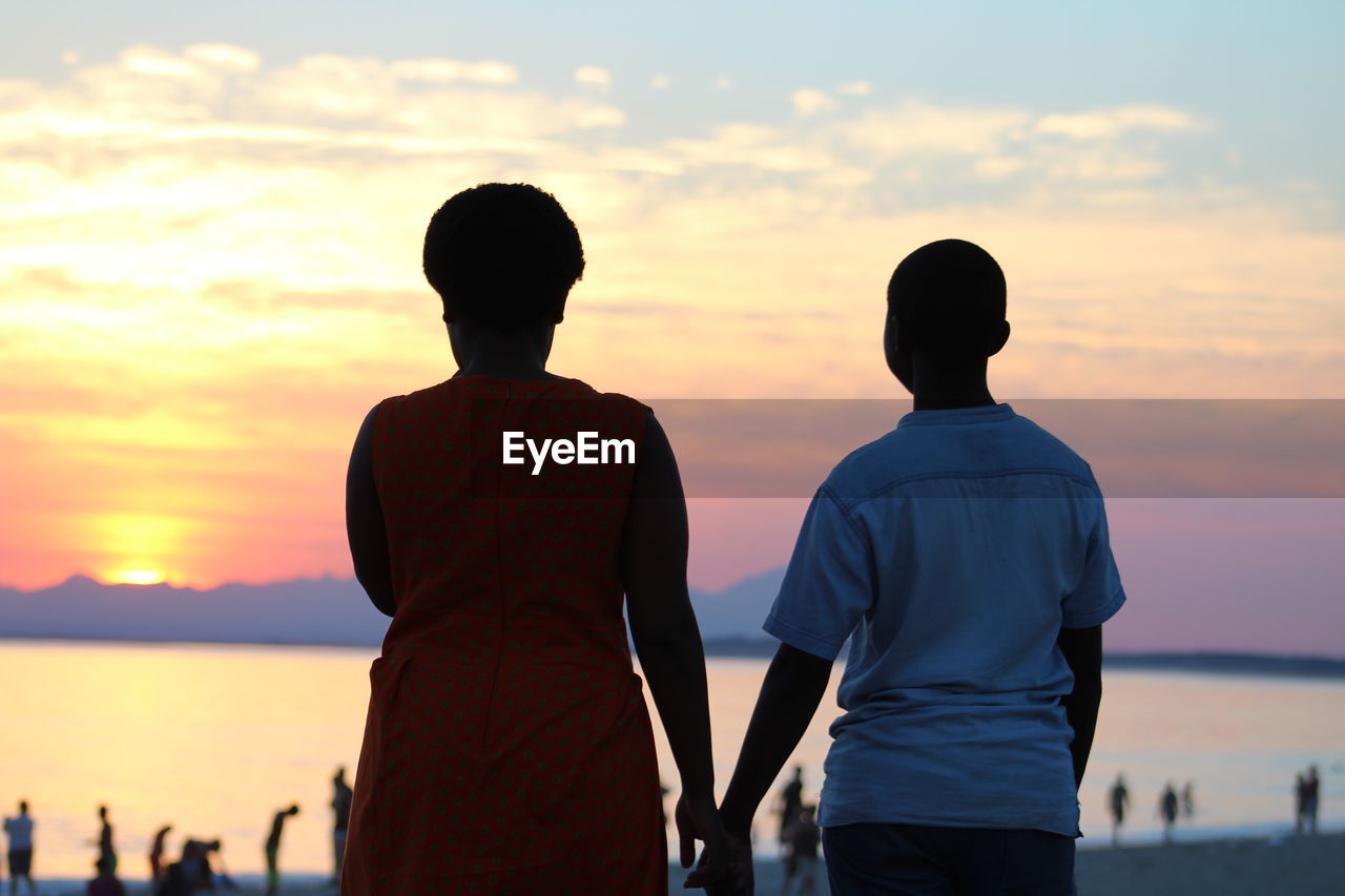 Rear View Of Silhouette Couple Standing Against Sea During Sunset