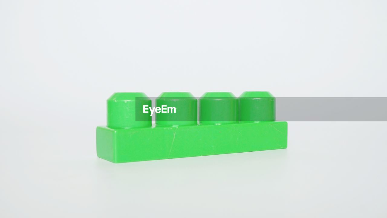CLOSE-UP OF GREEN TOY AGAINST WHITE BACKGROUND