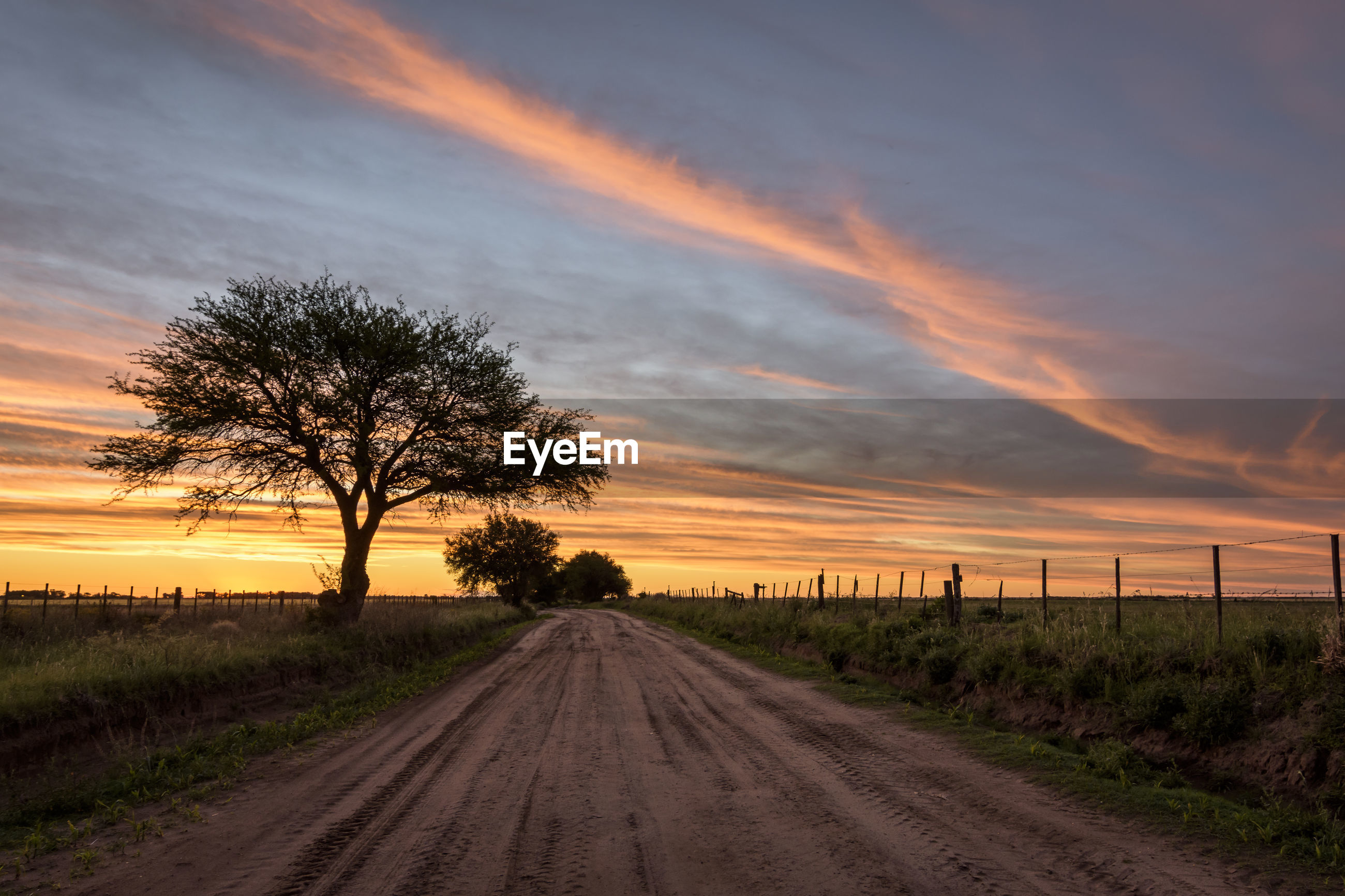 Dirt road against dramatic sky during sunset