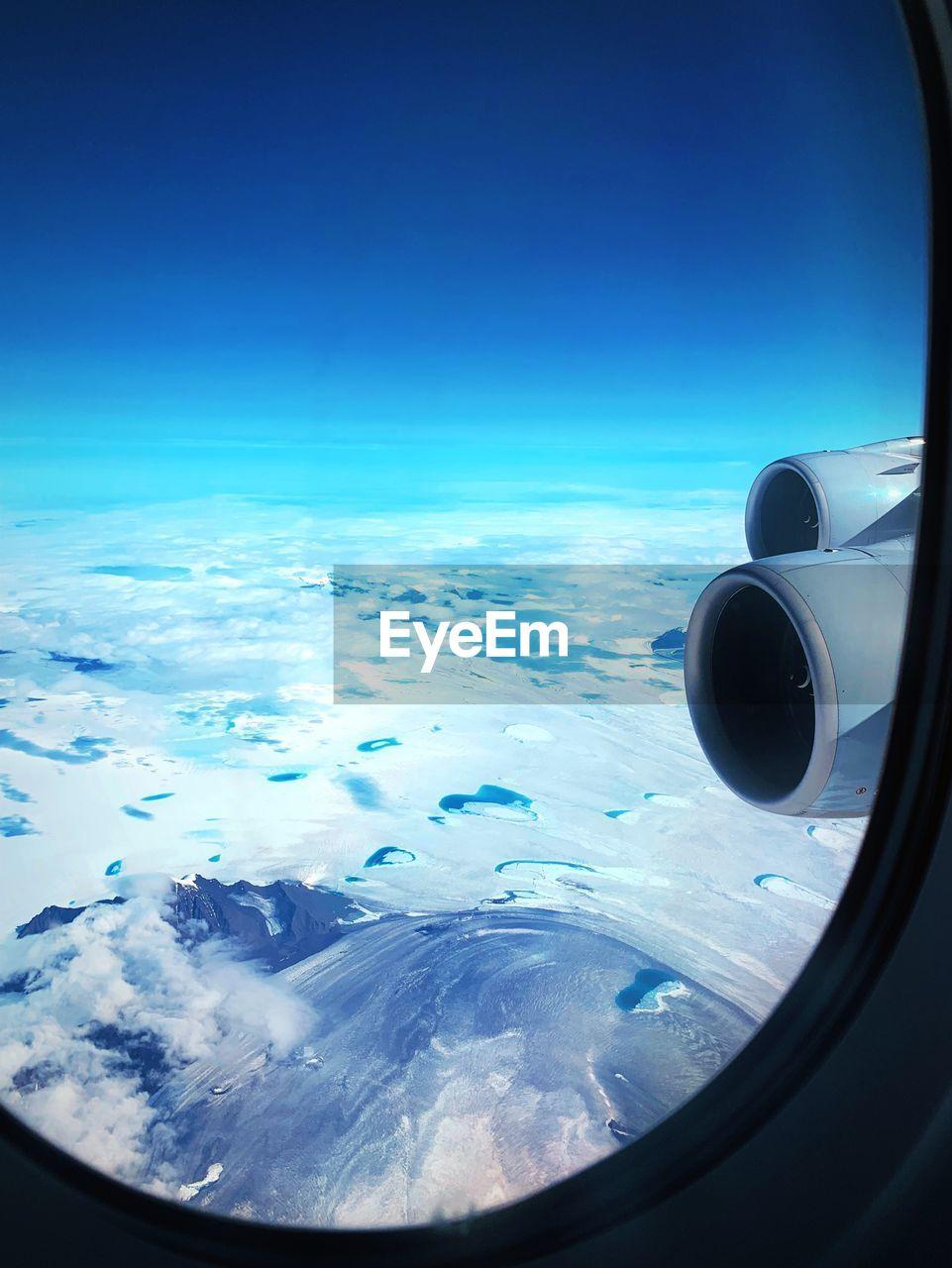 Sky seen through airplane window against blue sky