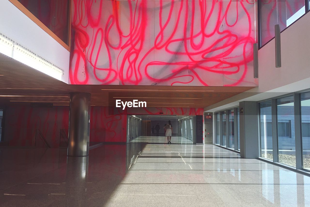 architecture, built structure, indoors, building, flooring, red, corridor, no people, arcade, empty, day, glass - material, entrance, reflection, door, architectural column, illuminated, absence, tiled floor, ceiling