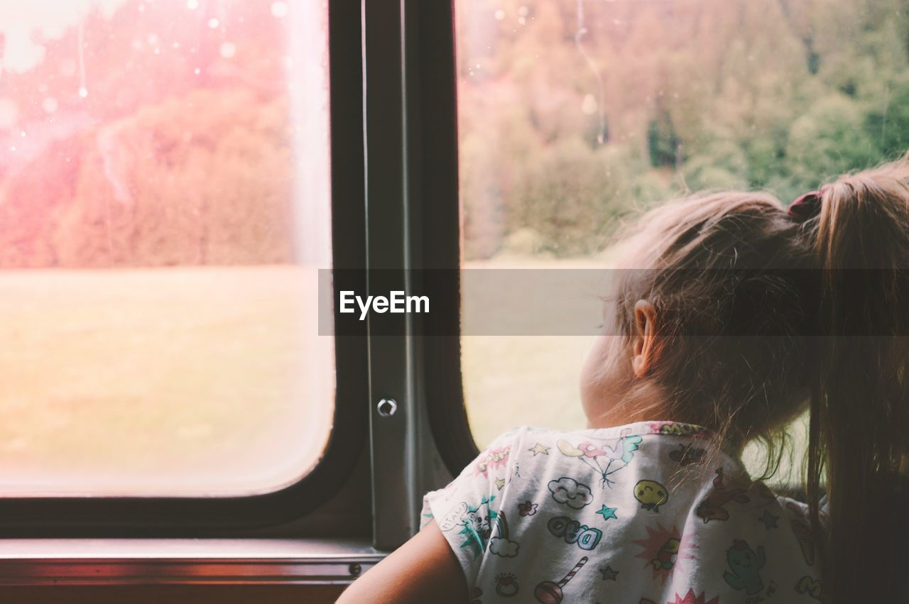 Rear View Of Girl Looking Through Window While Traveling In Train