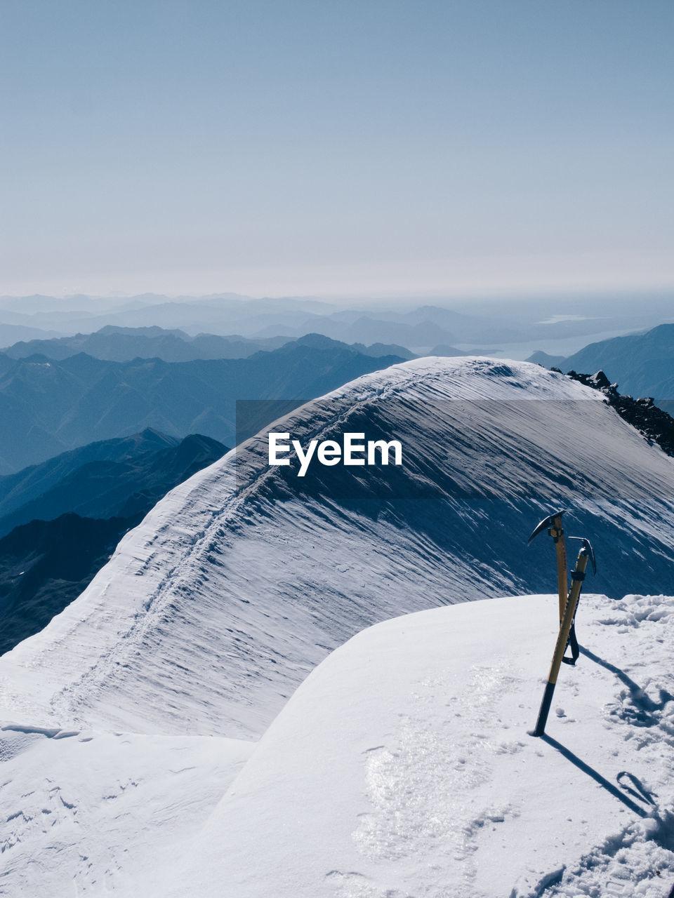 Ice Axes On Snowcapped Mountain Against Clear Sky