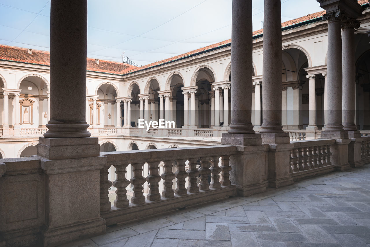 architectural column, architecture, built structure, history, the past, arch, arcade, building exterior, no people, building, day, nature, colonnade, travel destinations, in a row, sky, corridor, railing, outdoors, courtyard, balustrade, ornate, courthouse