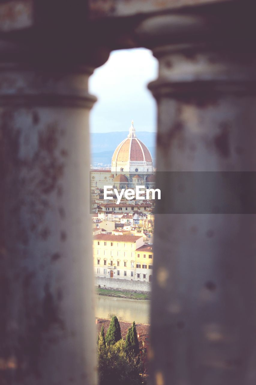 Florence cathedral by buildings against sky