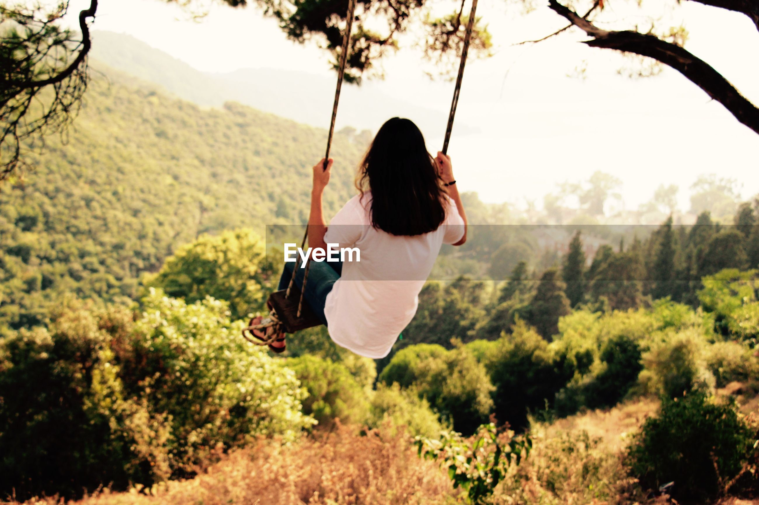 Rear view of woman on rope swing against mountains