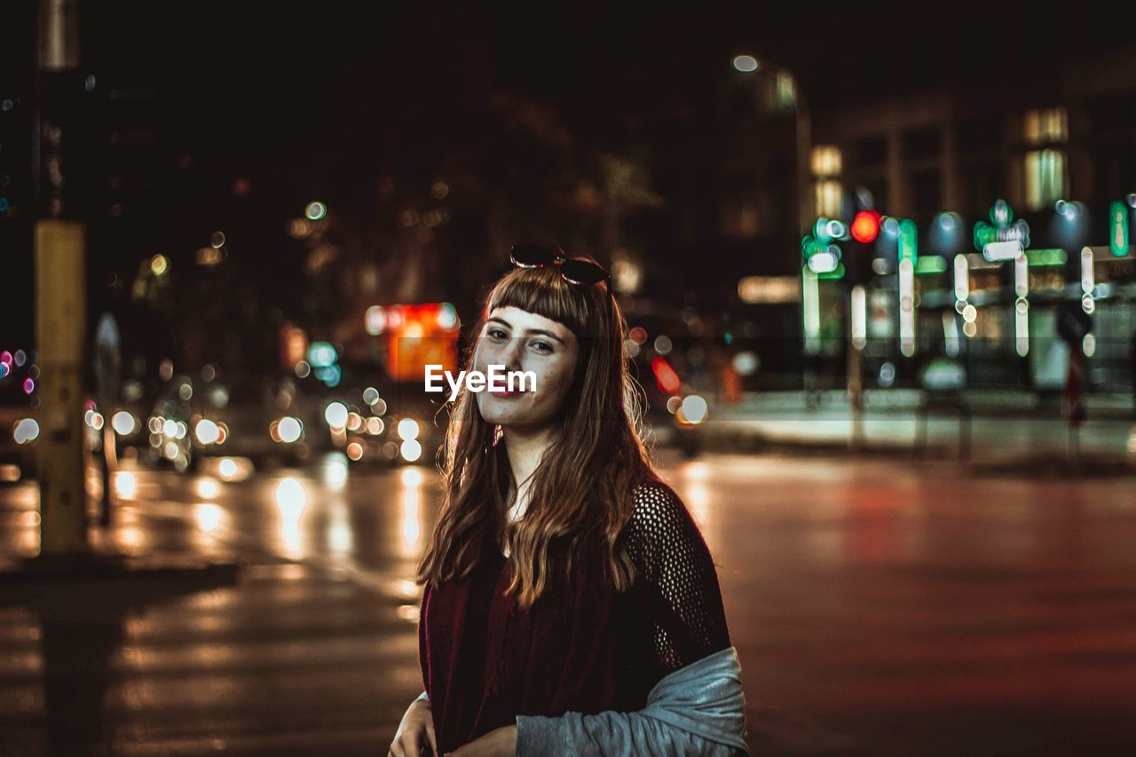 Portrait Of Smiling Teenage Girl Standing On Street In Illuminated City At Night