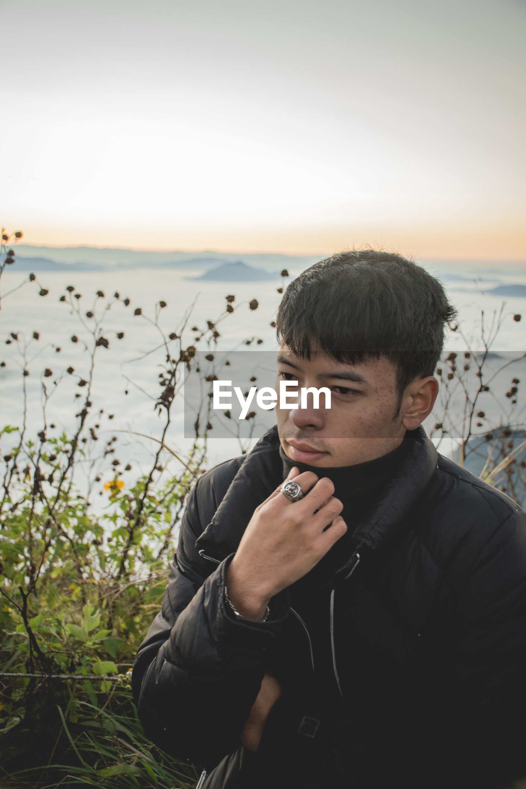 Thoughtful young man looking away while standing on mountain peak