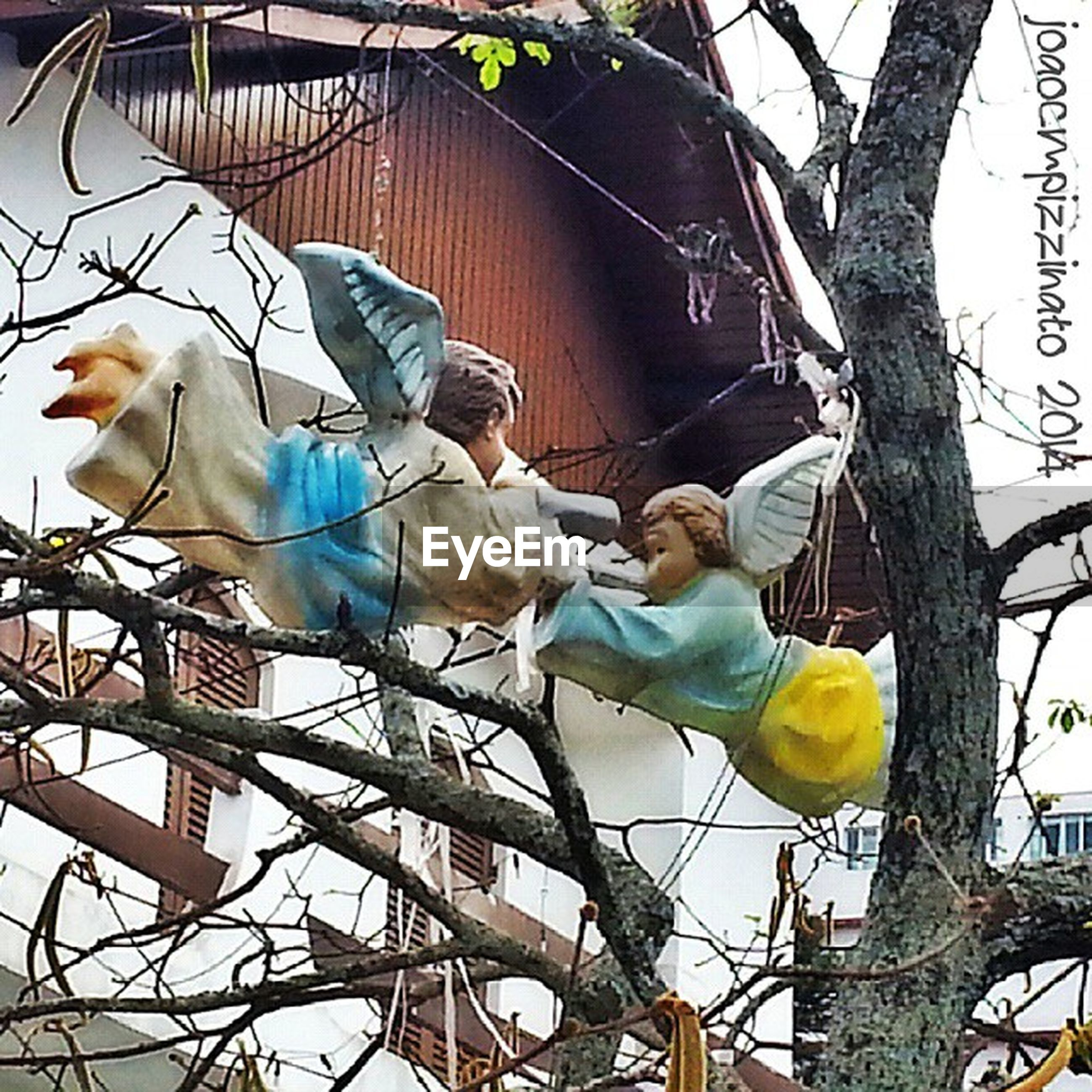 low angle view, animal themes, horse, bird, sky, amusement park, amusement park ride, architecture, built structure, outdoors, day, building exterior, clear sky, two animals, animal representation, domestic animals, fence, one animal, perching