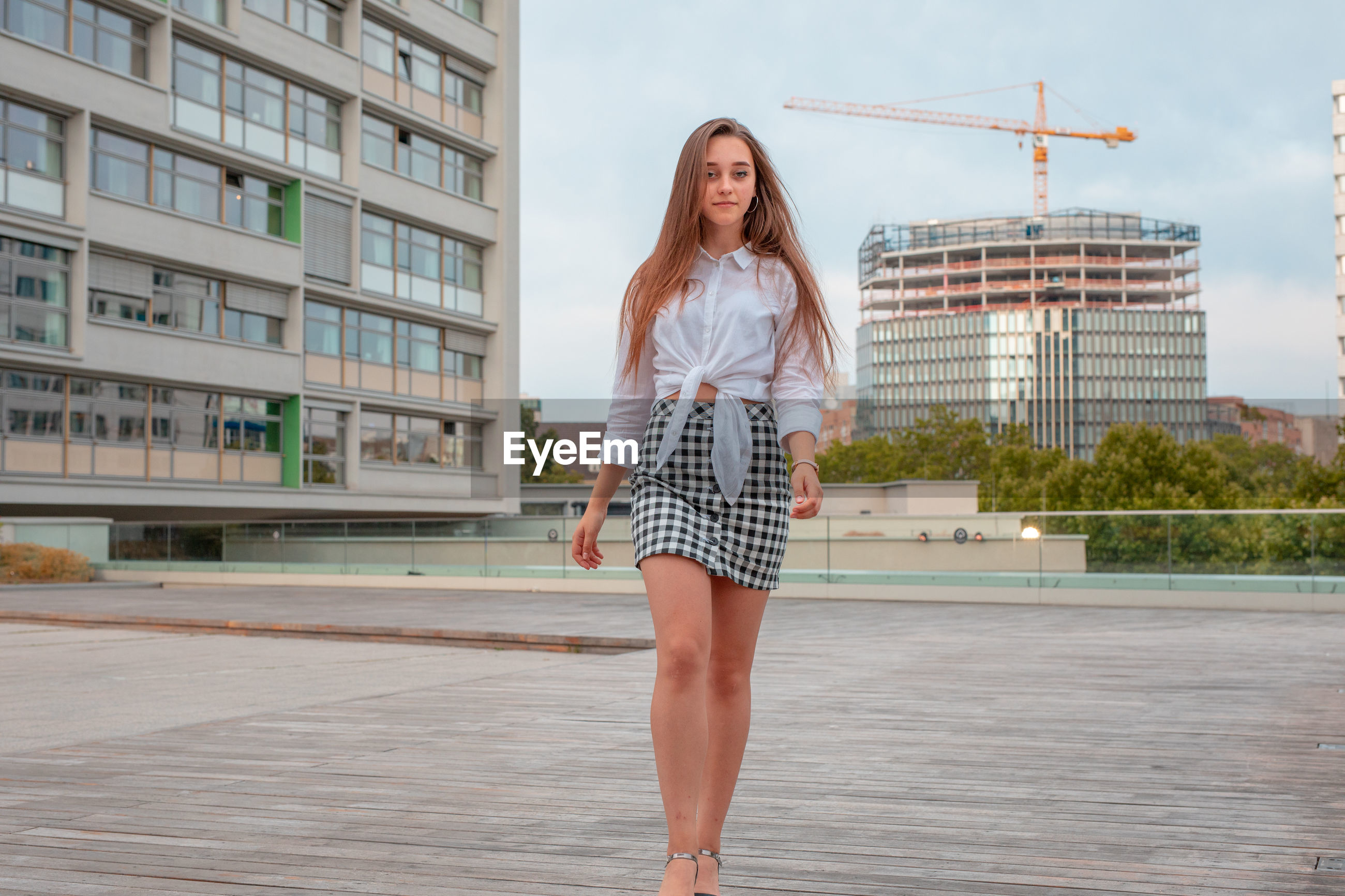Portrait of beautiful young woman standing against buildings in city