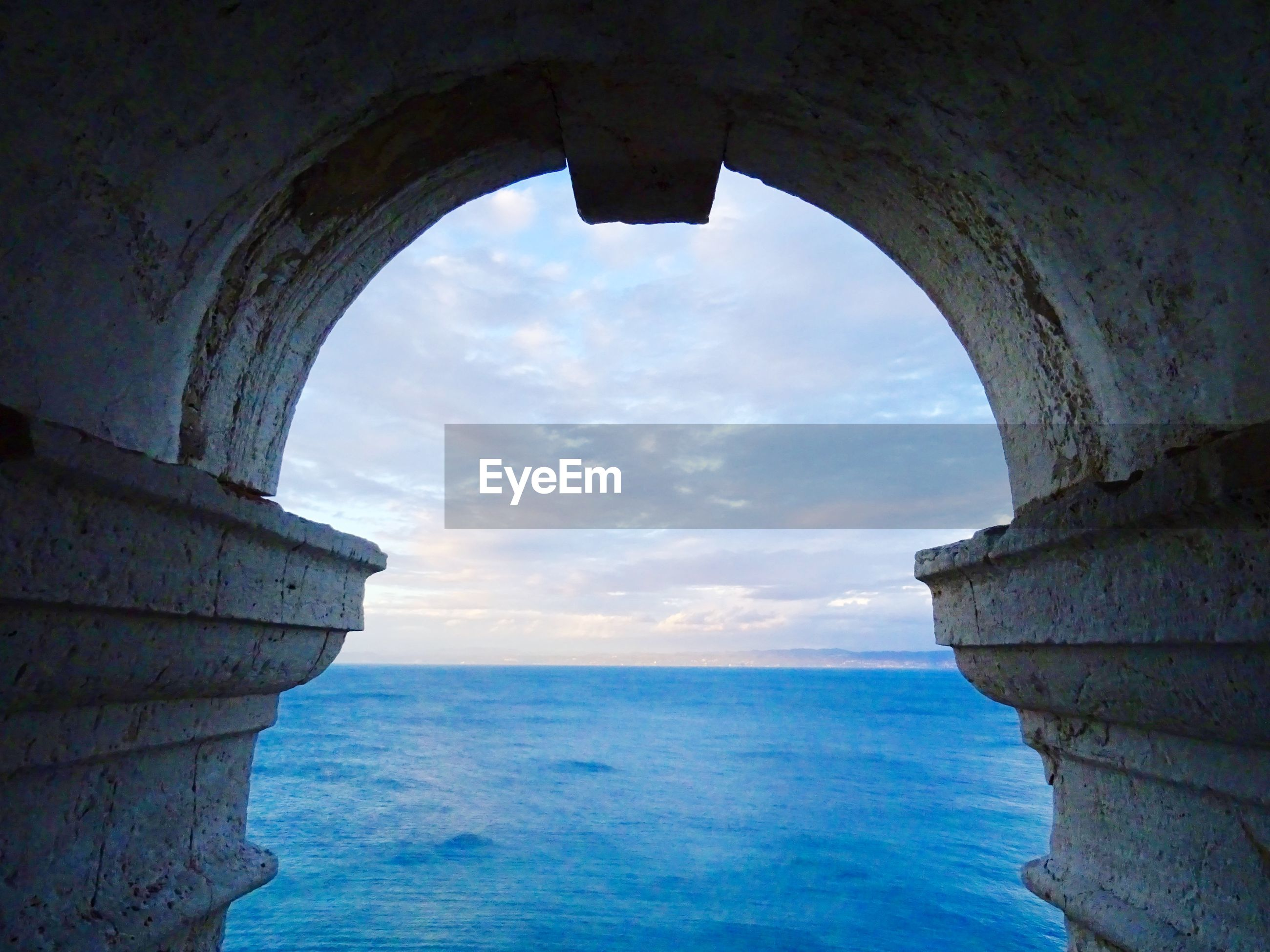 Scenic view of sea seen through arch
