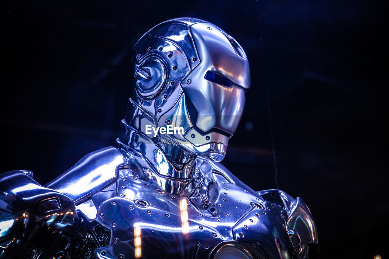 metal, night, motorcycle, no people, arts culture and entertainment, illuminated, representation, technology, mode of transportation, helmet, shiny, headwear, sculpture, human representation, blue, transportation, art and craft, indoors, land vehicle, close-up, chrome, silver colored