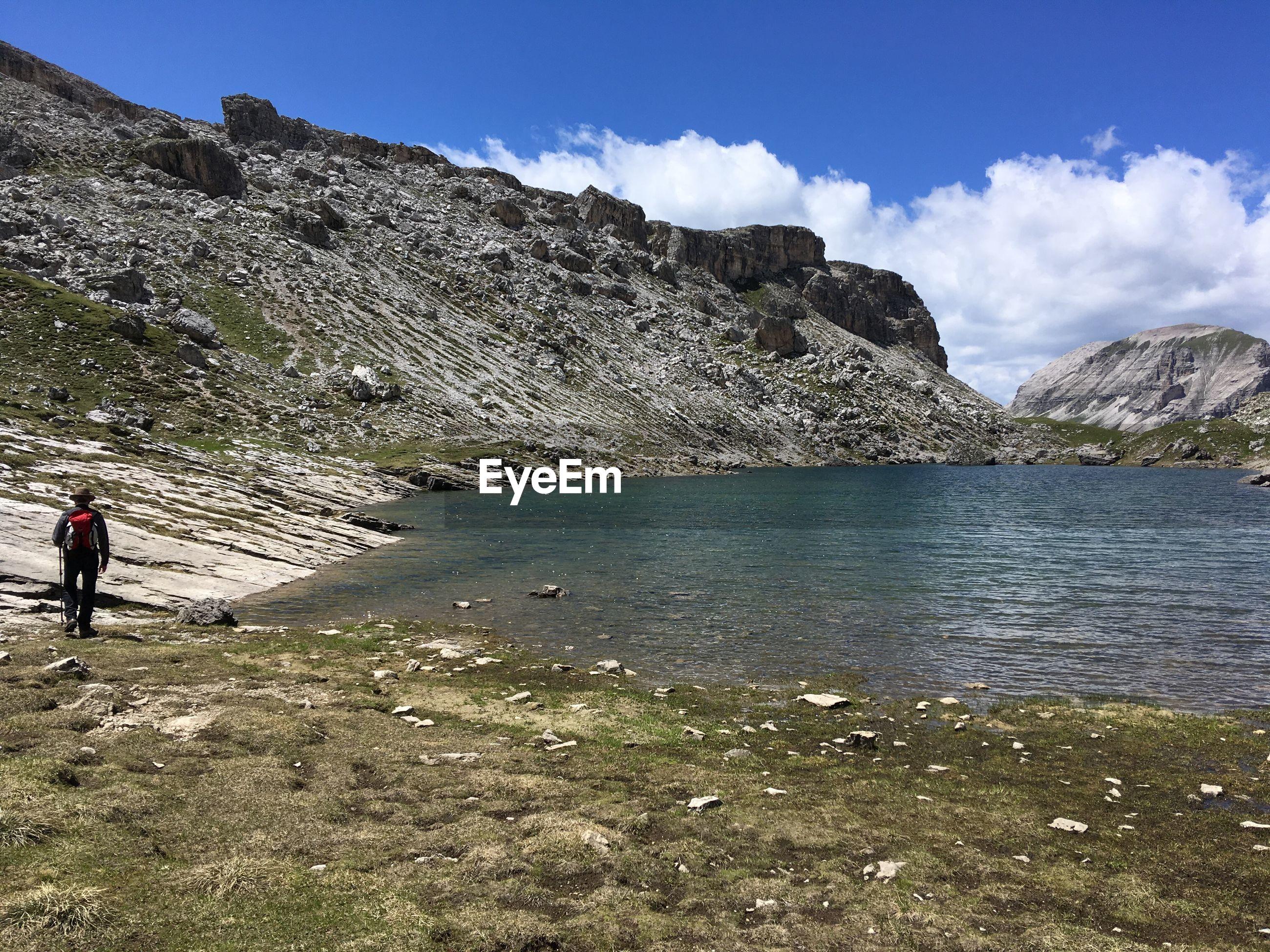 rocks by lake against sky in the dolomites, near passo gardena