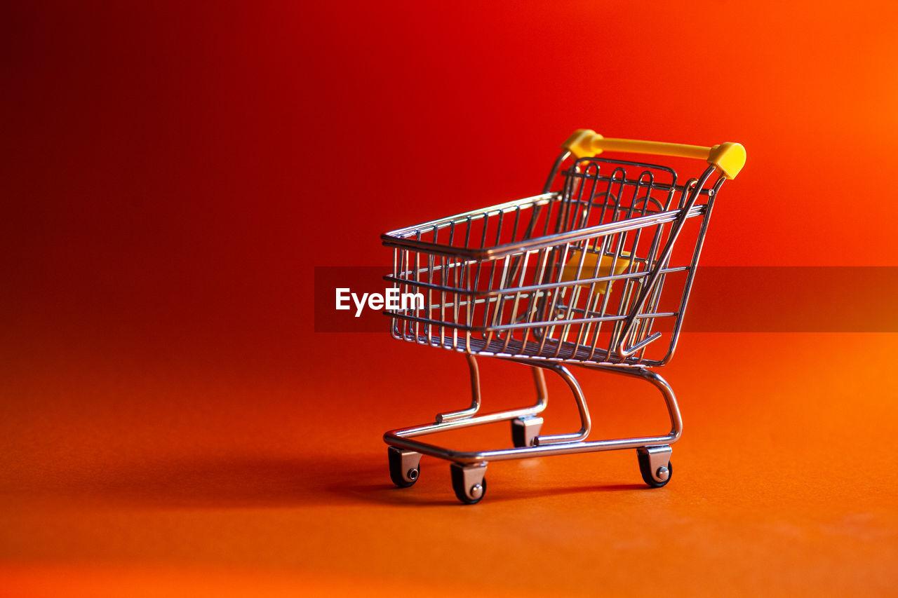 Small shopping cart on orange background