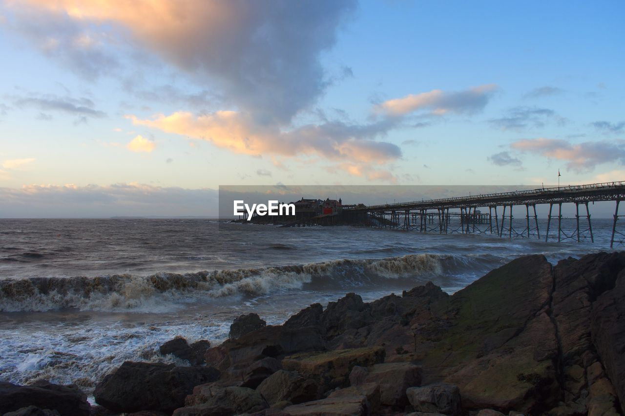 water, sea, sky, sunset, cloud - sky, nature, beauty in nature, built structure, architecture, scenics, outdoors, travel destinations, tranquil scene, no people, bridge - man made structure, motion, horizon over water, wave, beach, day