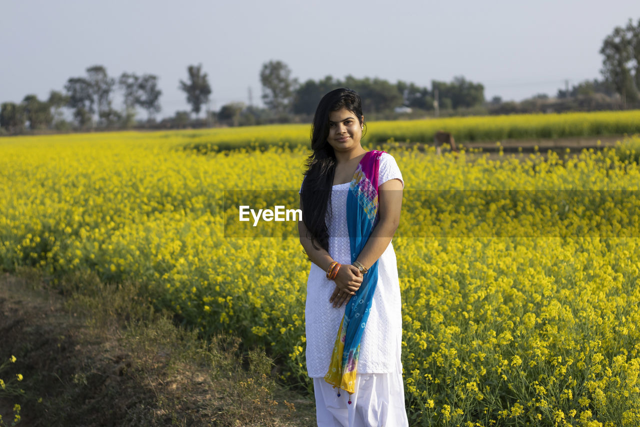 YOUNG WOMAN STANDING ON FIELD WITH YELLOW FLOWERS