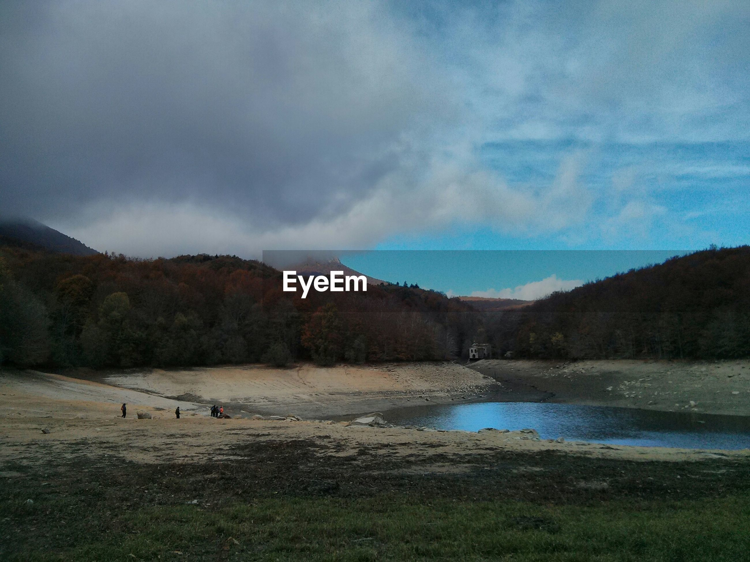 Scenic view of lake and trees against cloudy sky