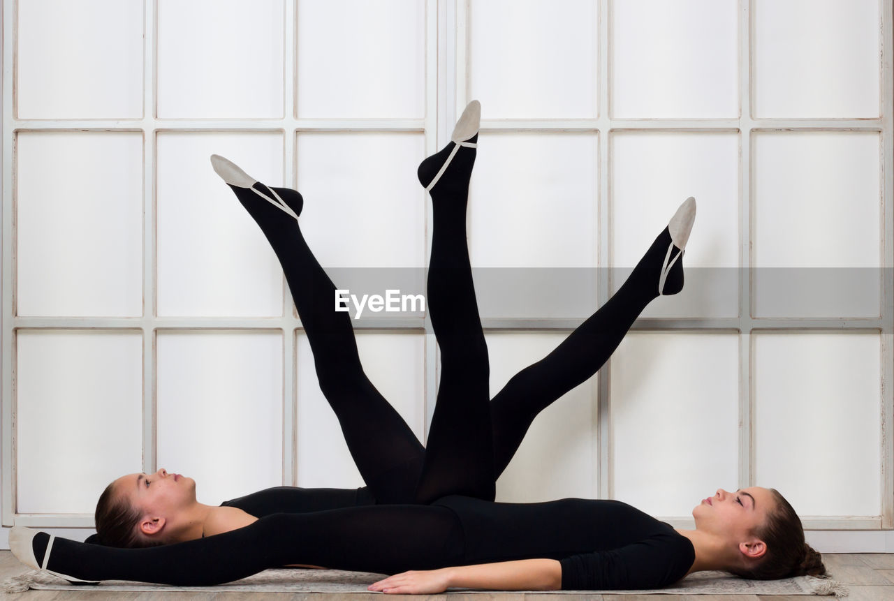 indoors, young adult, one person, exercising, young women, full length, real people, lying down, lifestyles, healthy lifestyle, leisure activity, flexibility, practicing, lying on back, stretching, women, relaxation, clothing, beautiful woman