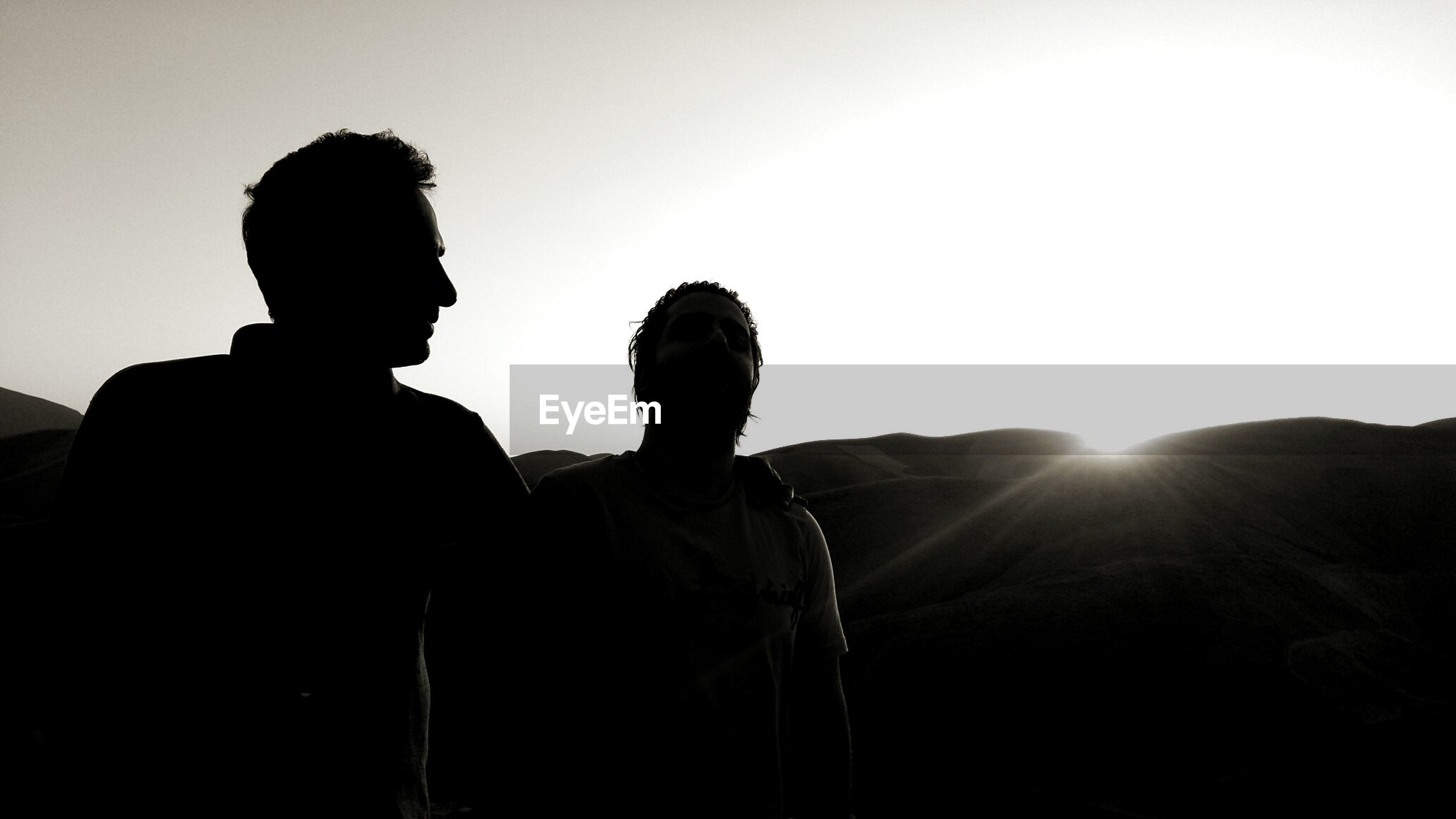 Silhouette friends standing on mountain against sky during sunset