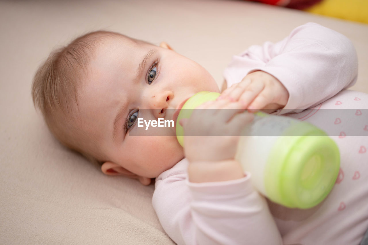 High angle portrait of cute baby girl drinking milk while lying on bed