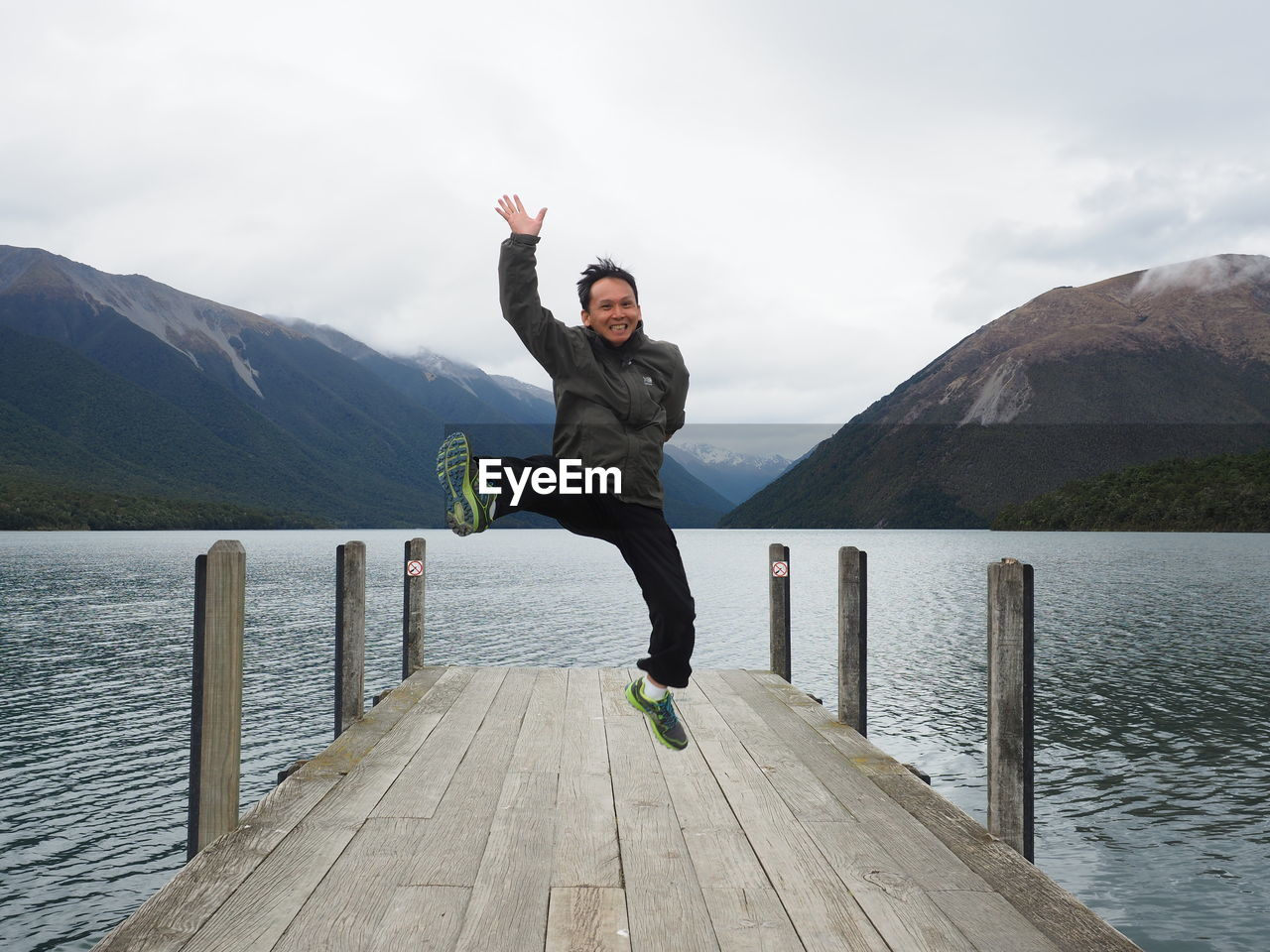 Portrait Of Cheerful Man Jumping On Pier Over Lake Against Mountains